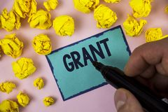 Word writing text Grant. Business concept for Money given by an organization or government for a purpose Scholarship written by Ma. N Sticky note paper holding Royalty Free Stock Images