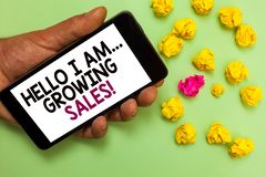 Word writing text Hello I Am... Growing Sales. Business concept for Making more money Selling larger quantities Man. Holding cell phone white screen looking royalty free stock image
