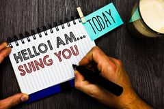 Word writing text Hello I Am... Suing You. Business concept for create a case to accuse someone from his actions Man holding marke. R notebook clothespin hold Royalty Free Stock Photography
