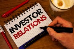 Word writing text Investor Relations. Business concept for Finance Investment Relationship Negotiate Shareholder Hand grasp black. Marker wooden desk red pen stock photo