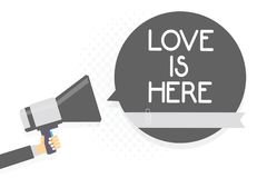 Word writing text Love Is Here. Business concept for Romantic feeling Lovely emotion Positive Expression Care Joy Man holding mega. Phone loudspeaker gray speech royalty free stock photo