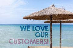 Word writing text We Love Our Customers Call. Business concept for Client deserves good service satisfaction respect Blue beach wa. Ter Thatched Straw Umbrellas Stock Images