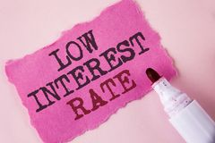 Word writing text Low Interest Rate. Business concept for Manage money wisely pay lesser rates save higher written on Tear Pink St. Word writing text Low stock photography