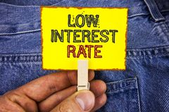 Word writing text Low Interest Rate. Business concept for Manage money wisely pay lesser rates save higher written on Yellow Stick. Word writing text Low royalty free stock images
