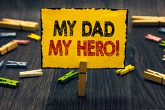 Word writing text My Dad My Hero. Business concept for Admiration for your father love feelings emotions compliment. Blacky wooden desk laid paper clip randomly stock images