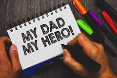 Word writing text My Dad My Hero. Business concept for Admiration for your father love feelings emotions compliment Hand holding p. En and paper sketch words stock image