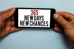 Word writing text 365 New Days New Chances. Business concept for Starting another year Calendar Opportunities Human hand hold smar. Tphone with red and black royalty free stock photos