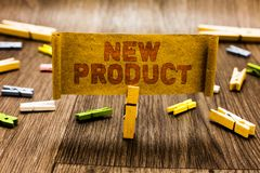 Word writing text New Product. Business concept for goods and services that differ in their characteristics Clothespin holding old stock photos