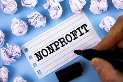 Word writing text Nonprofit. Business concept for Activities that do not generate revenues to the executor written by Man on Notep. Word writing text Nonprofit Royalty Free Stock Photo