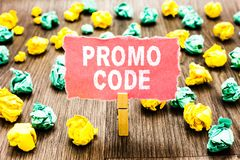 Word writing text Promo Code. Business concept for digital numbers that give you good discount on certain product Clothespin holdi. Ng pink note paper crumpled stock photo