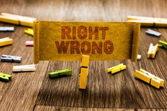 Word writing text Right Wrong. Business concept for choose between two decisions correct and bad one to make Clothespin holding ol. D piece fabric several royalty free stock photos