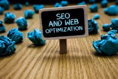 Word writing text Seo And Web Optimization. Business concept for Search Engine Keywording Marketing Strategies Paperclip hold blac. K paperboard with text blue stock photos