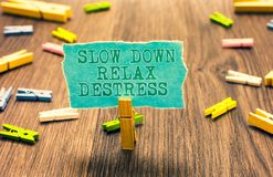 Word writing text Slow Down Relax Destress. Business concept for calming bring happiness and put you in good mood Clothespin holdi. Ng turquoise paper note Stock Image