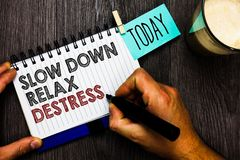 Word writing text Slow Down Relax Destress. Business concept for calming bring happiness and put you in good mood Man holding mark. Er notebook clothespin hold Stock Photography