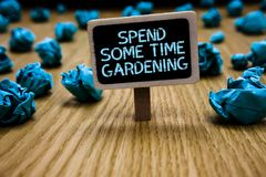 Word writing text Spend Some Time Gardening. Business concept for Relax planting flowers fruits vegetables Natural Paperclip hold. Black paperboard with text stock images