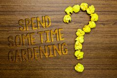 Word writing text Spend Some Time Gardening. Business concept for Relax planting flowers fruits vegetables Natural Wooden floor wi. Th some letters yellow paper stock photography