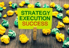 Word writing text Strategy Execution Success. Business concept for putting plan or list and start doing it well Clothespin holding. Yellow note paper crumpled stock photography