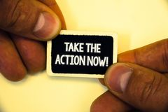 Word writing text Take The Action Now Motivational Call. Business concept for Act Start Promptly Immediate Instantly Two hands hol. D small black card focused stock photos