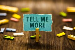 Word writing text Tell Me More. Business concept for A call to start a conversation Sharing more knowledge Clothespin holding blue. Paper note reminder royalty free stock photos