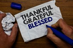 Word writing text Thankful Grateful Blessed. Business concept for Appreciation gratitude good mood attitude Hand hold paper lob an. D blue marker wooden base royalty free stock image