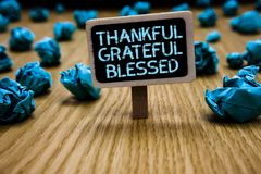 Word writing text Thankful Grateful Blessed. Business concept for Appreciation gratitude good mood attitude Paperclip hold black p. Aperboard with text blue royalty free stock photo