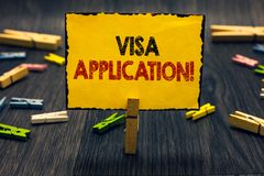 Word writing text Visa Application. Business concept for Form to ask permission travel or live in another country Blacky. Wooden desk laid paper clip randomly stock photography