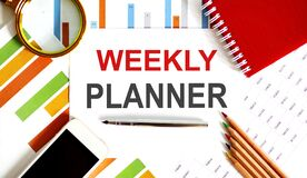 Word writing text WEEKLY PLANNER on notepad. Business concept with office tools on the chart background