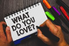 Word writing text What Do You Love question. Business concept for Enjoyable things passion for something inspiration Hand holding. Pen and paper sketch words royalty free stock image