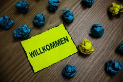 Word writing text Willkommen. Business concept for welcoming people event or your home something to that effect Yellow piece paper royalty free stock images