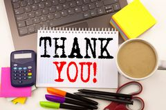 Word writing Thank You in the office with surroundings such as laptop, marker, pen, stationery, coffee. Business concept for Givin Stock Photo