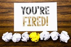 Word, writing You Are Fired. Concept for Unemployed or Discharge Written on sticky note paper reminder, wooden background with sti stock image