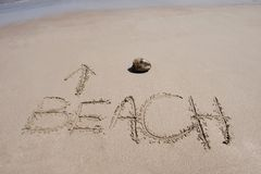 Word written in sand on tropical beach & coconut. Word beach written in sand on costa rican tropical beach with coconut in scene Stock Photography