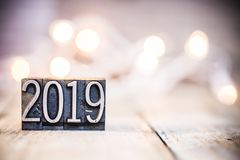 2019 Concept Vintage Letterpress Type Theme. The word 2019 written in vintage metal letterpress type on a bokeh light and wooden background stock photos