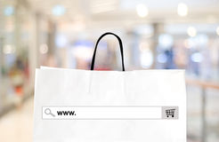 Word www. on search bar over shopping bag and blur store backgro Royalty Free Stock Image