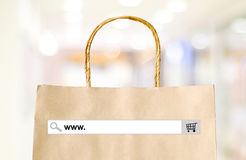 Word www. on search bar over shopping bag and blur store backgro Royalty Free Stock Photos