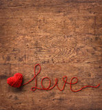 The word 'love' written of red wool yarn on wooden background. Royalty Free Stock Photography