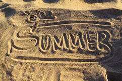Word 'Summer' handwritten on the sand, top view. Stock Photos