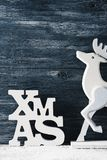 Word xmas, abbreviation for Christmas, and white reindeer stock images