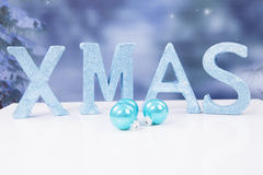 The word Xmas in blue glitter letters and balls Stock Photos