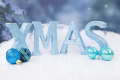 The word Xmas in blue glitter letters and balls Royalty Free Stock Photos