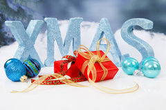 The word Xmas in blue glitter letters with balls and presents Royalty Free Stock Photography