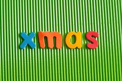 The word Xmas in colorful letters. On a green background Royalty Free Stock Photography