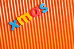 The word Xmas in colorful letters. On an orange background Stock Photography