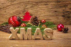 The word xmas in front of a wooden background Royalty Free Stock Photography