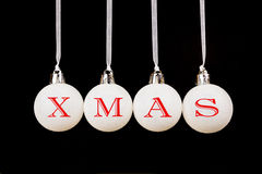 Word xmas on white christmas balls hanging on black background Royalty Free Stock Photos