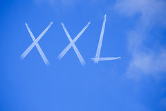 Word XXL on blue sky. Planes made the word XXL on blue sky Royalty Free Stock Photography