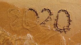 Word 2020 year painted at the sand is washed off by the wave