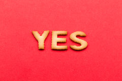 Word yes biscuit. Over the red background Stock Images