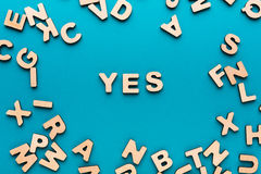 Word Yes on blue background. In wooden letters frame. Agreement, harmony, consensus concept stock photo
