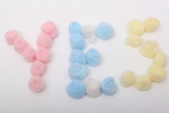 Word yes with cotton balls. Word yes with blue, yellow and pink hygienic cotton balls isolated on a white background Stock Photography